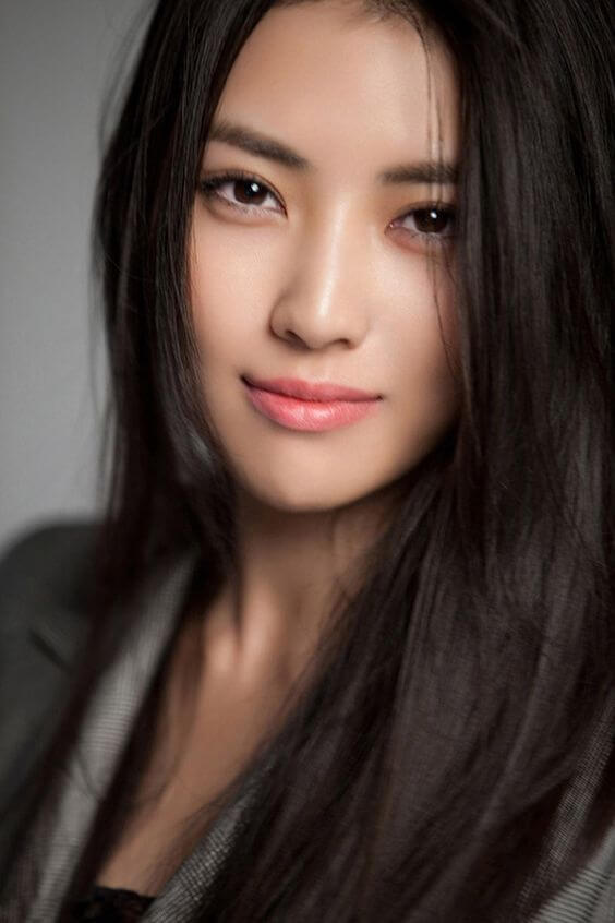 Headshot of Asian woman with eyeliner and light lip color