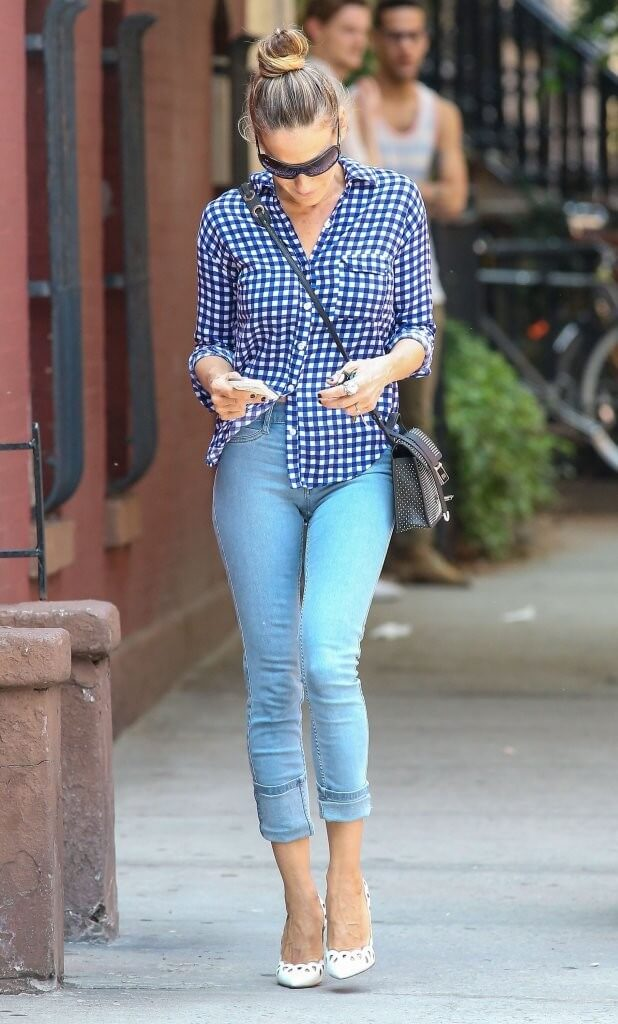 Sarah Jessica Parker wearing skinny cuffed blue jeans together with a blue-and-white gingham shirt and pointy white stiletto shoes