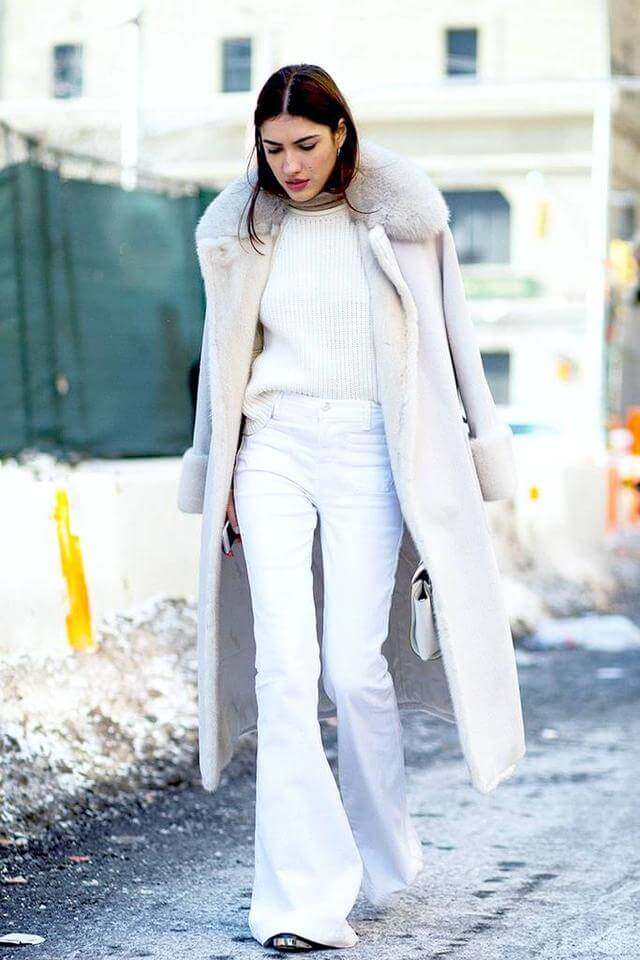 Tall brunette wearing white flared jeans with a white turtleneck and a nude coat