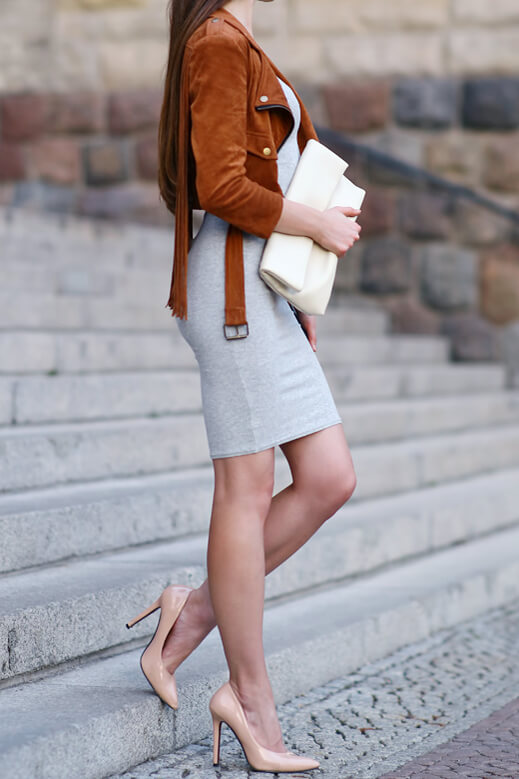 Woman on the stairs with brown leather jacket and mini skirt