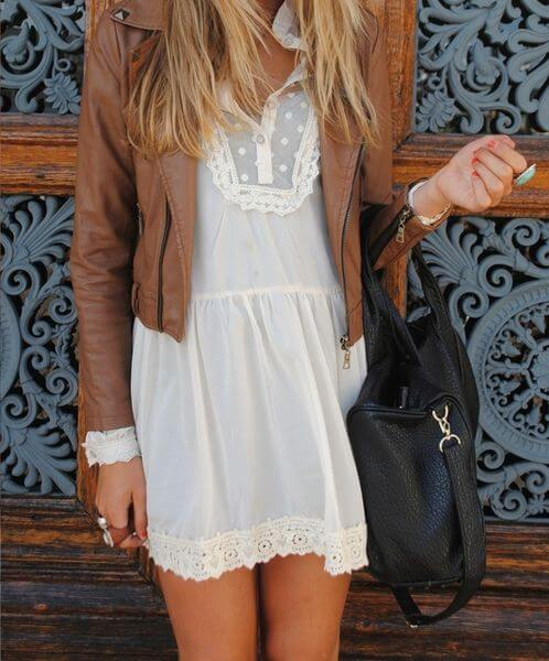 Woman in a white lace dress with a brown leather jacket and black handbag