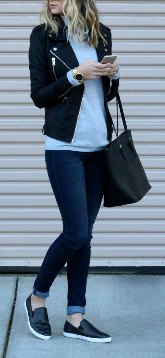 Woman in blue cuffed skinny jeans together with a grey T-shirt and black leather jacket