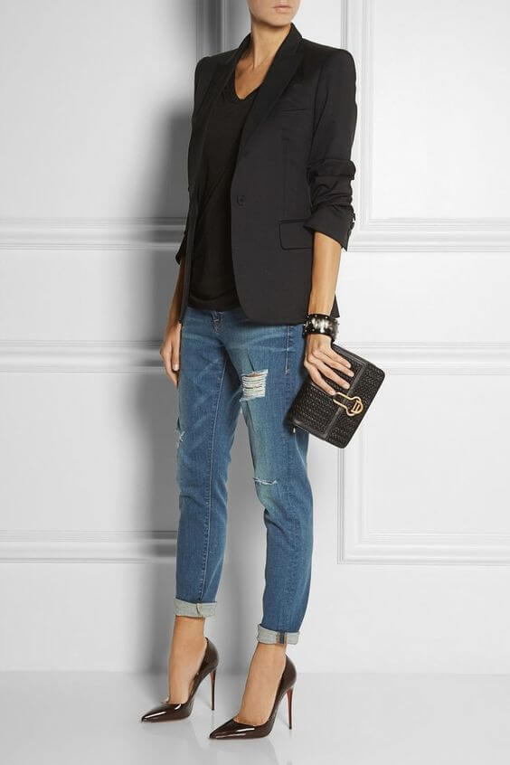 Woman in cuffed boyfriend jeans together with a black fitted blazer and black stiletto heels