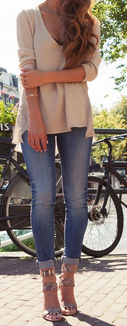Woman in cuffed skinny jeans and beige top with a bicycle next to a lake