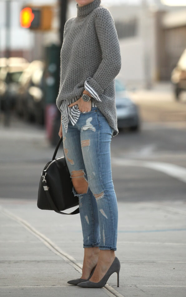 Woman in cuffed skinny jeans and grey turtleneck sweater with grey stilettos on the street