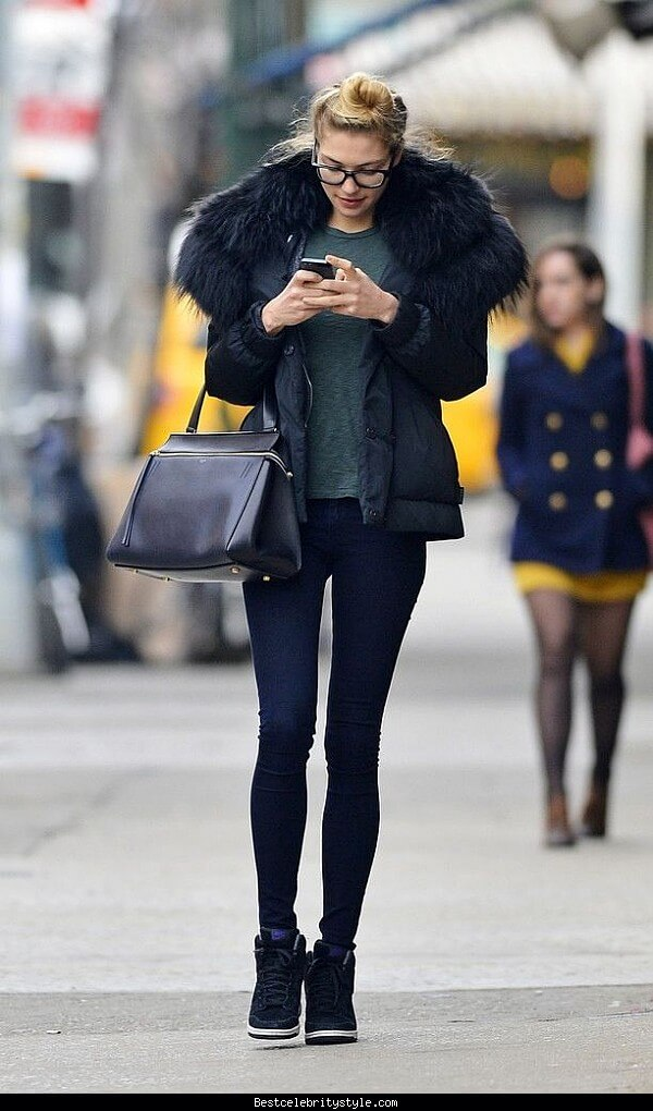 Woman in glasses wearing black jeans with a black puffer jacket