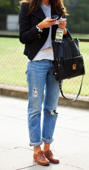 Woman in the park wearing blue cuffed boyfriend jeans with brown brogue shoes and a black military style jacket