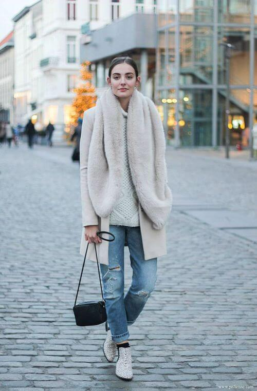 Woman on street wearing light blue jeans with a coat, and faux fur scarf