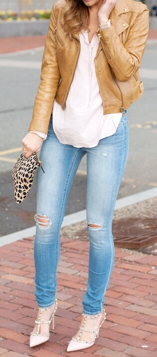 Woman on the sidewalk wearing blue skinny jeans, pale pink top and brown leather jacket with a leopard print clutch purse