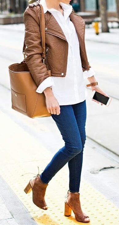 Woman on the sidewalk wearing blue skinny jeans, white blouse, brown leather jacket, brown peep-toe shoes and brown leather bag