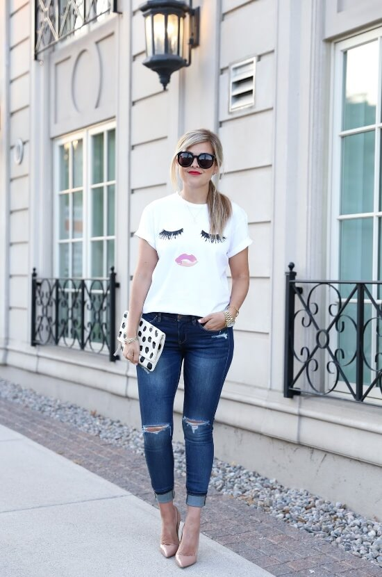 Woman on the sidewalk wearing ripped blue skinny cuffed jeans with a white T-shirt and nude pointy heels