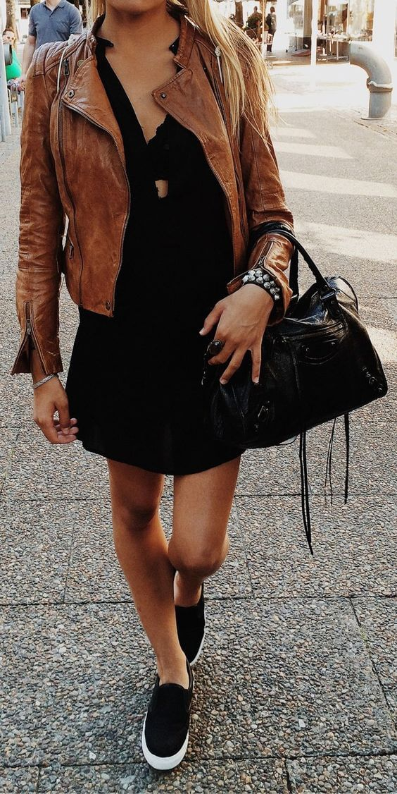 Woman on the street wearing a black dress, black Vans, brown leather jacket and a black handbag