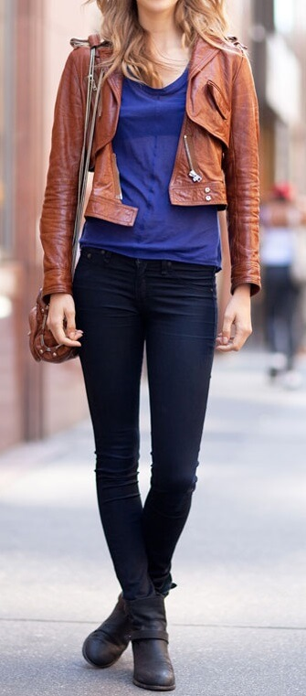 Woman on the street wearing dark blue skinny jeans, blue top, brown leather jacket and black ankle boots with a brown sling bag