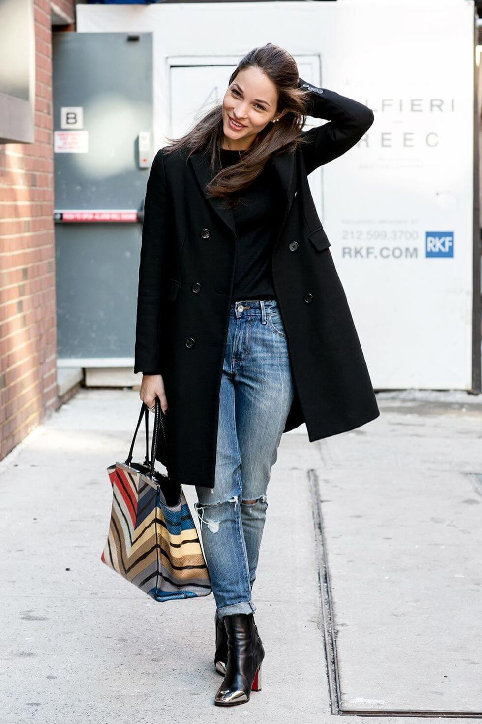 Woman wearing a black coat and black boots with blue high-waisted jeans
