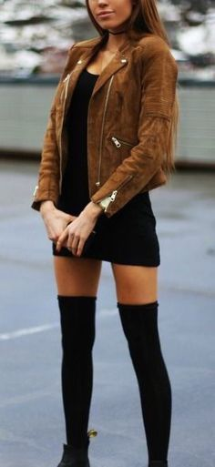 Woman wearing a black mini dress, brown leather jacket, black knee-high socks and black boots
