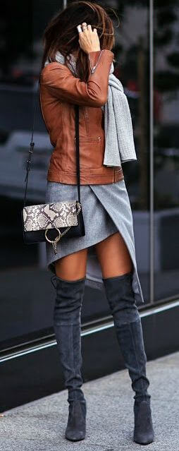 Woman wearing a gray dress, gray scarf, brown leather jacket and dark gray over-the-knee boots with a snakeskin sling handbag
