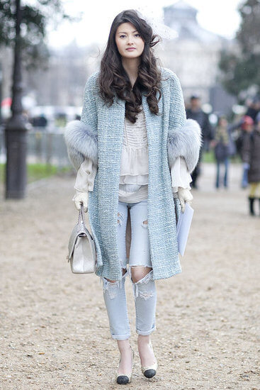 Woman wearing a ruffled top with light blue jeans and a pastel blue coat