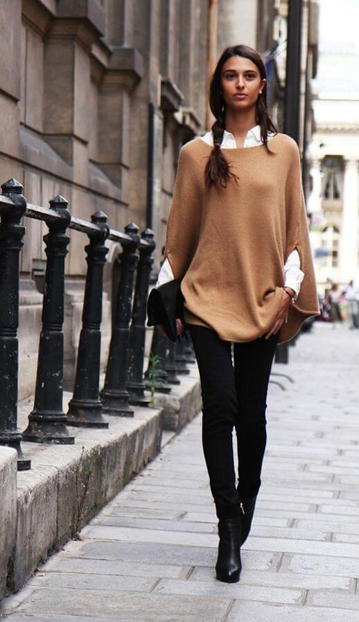 Woman wearing black jeans with a tan slouchy cape sweater