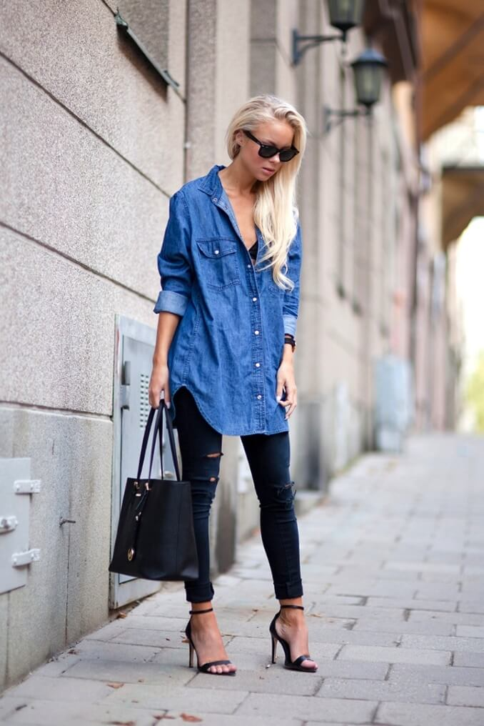 Woman on the city streets wearing black ripped denim jeans and blue denim shirt with black strappy sandals