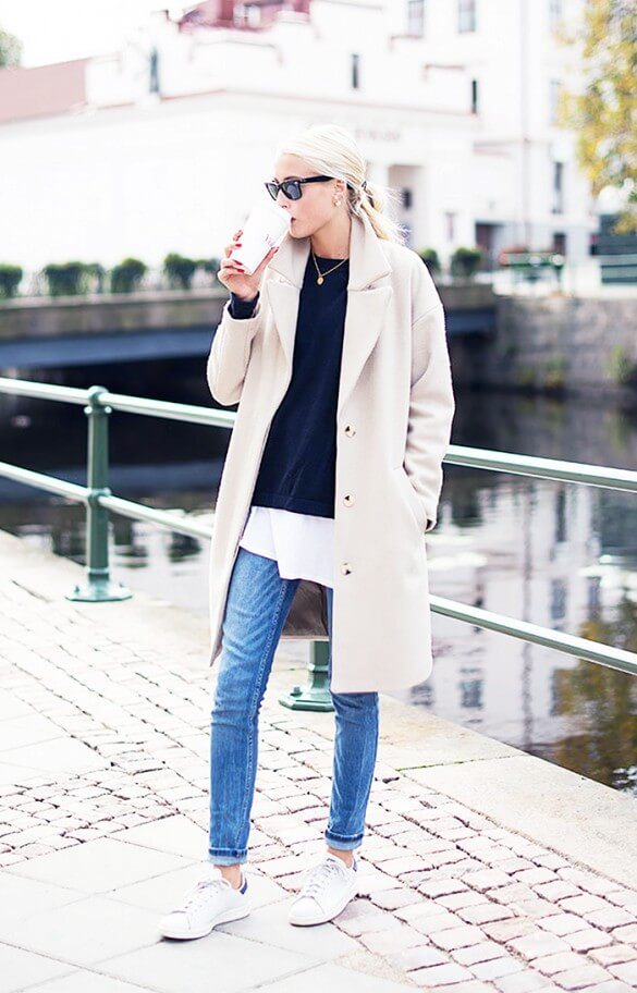 A woman in blue skinny jeans cuffed at the ankles with white trainers and a long beige coat