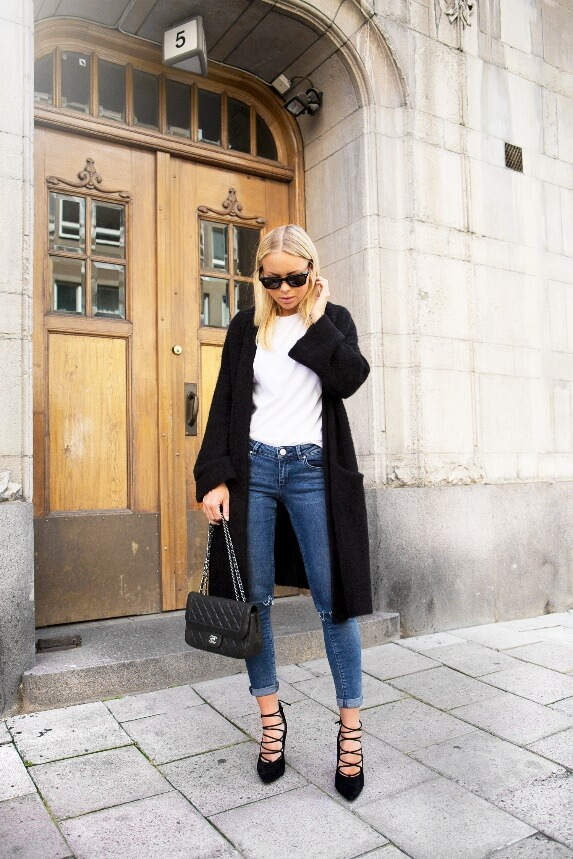 Woman wearing blue skinny jeans with a white T-shirt, long black cardigan and black strappy shoes