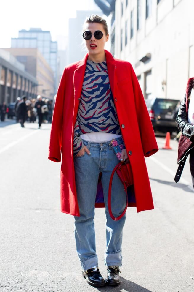 Woman wearing boyfriend jeans, an abstract top, and a bright red coat