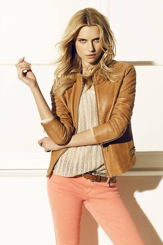 Woman wearing coral skinny jeans, beige top and brown leather jacket