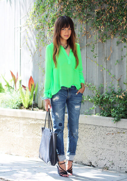 Woman wearing cuffed boyfriend jeans together with a bright green shirt and black strappy sandals