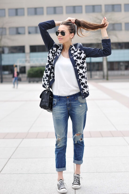 Woman in the city wearing cuffed boyfriend jeans with Converse sneakers, a white T-shirt and patterned bomber jacket