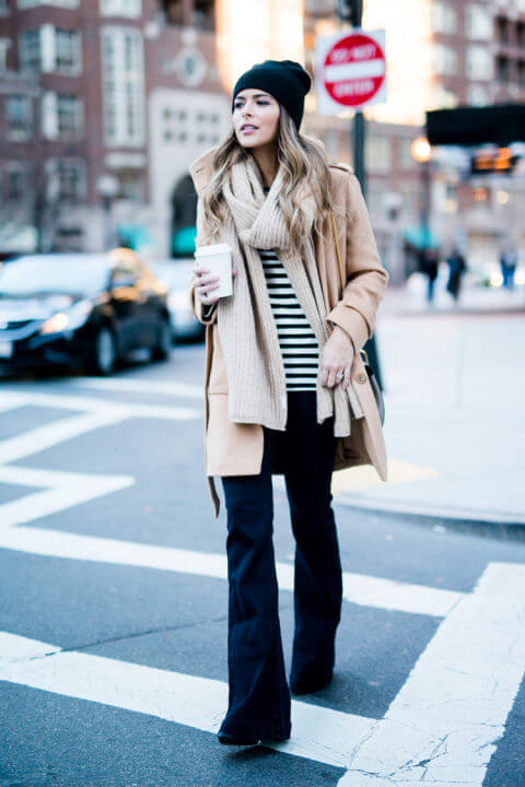 Woman wearing dark wash flared jeans, with a striped top, tan coat, and a scarf
