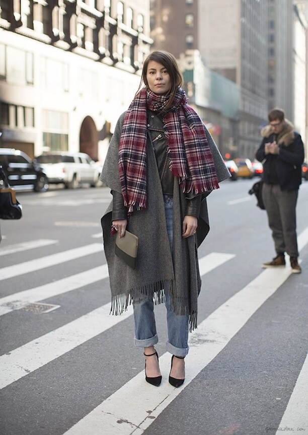 Woman wearing jeans with a plaid scarf and an oversized blanket coat