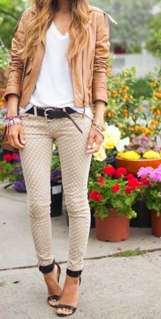 Woman wearing patterned pants, white top and brown leather jacket with ankle strap stiletto heels