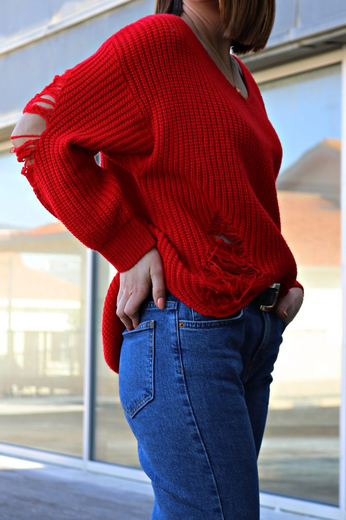 Woman wearing red sweater and blue jeans