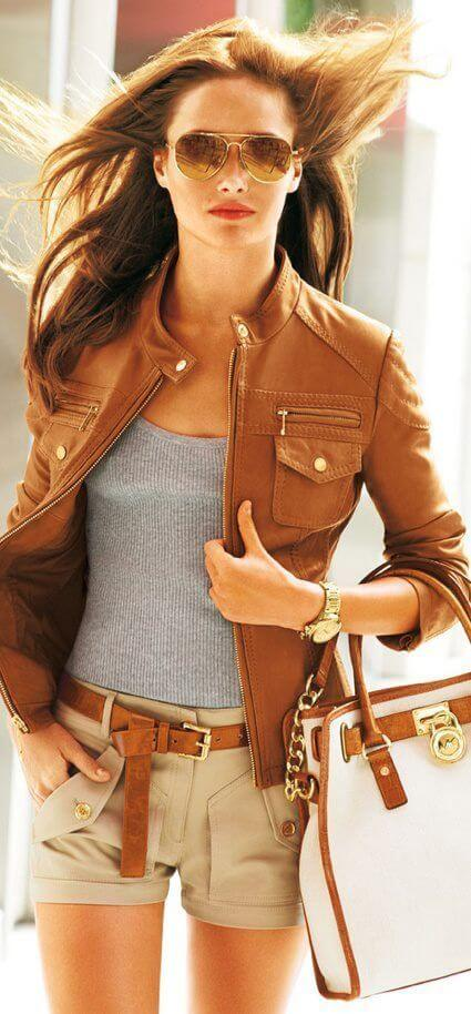 Woman wearing tan shorts, gray tank top, brown leather jacket and white leather handbag