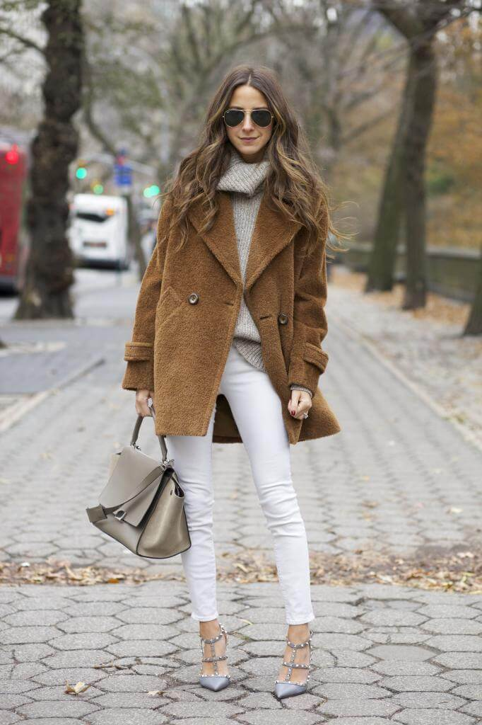 Woman wearing white jeans, a grey turtleneck, and a brown coat
