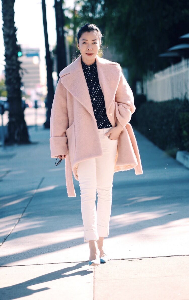 Woman wearing white jeans with a blush pink coat.