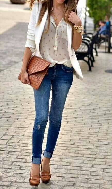 Woman on the streets of the city in blue cuffed skinny jeans with a loose silk shirt and white blazer