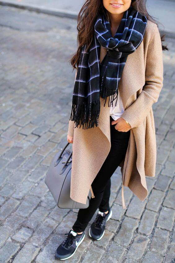 A blogger is wearing scarf and coat