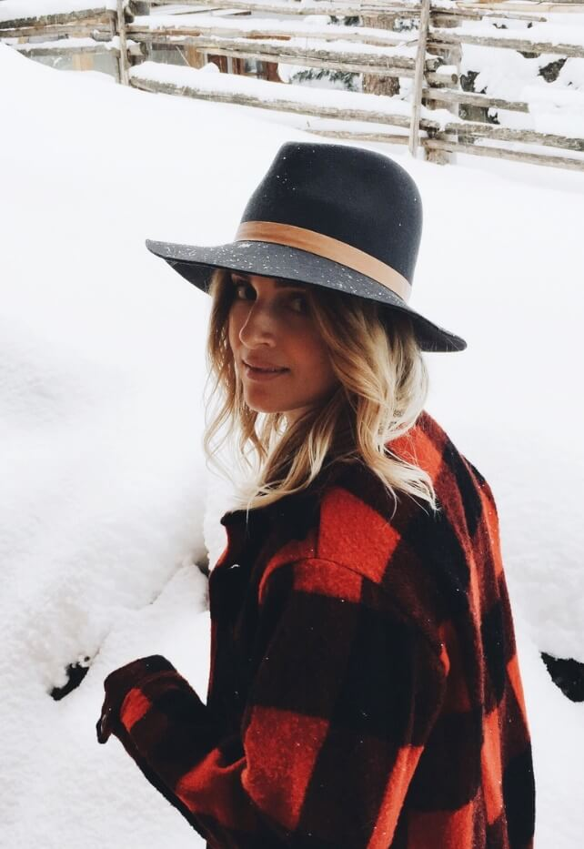 A woman with a grey hat and a plaid coat