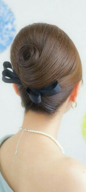 Beehive hairstyle with a French twist and black ribbon bow