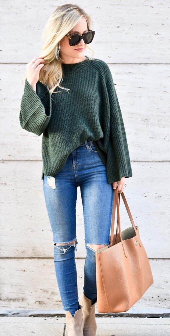 Blonde wearing ripped blue high-waisted jeans and olive green tucked sweater
