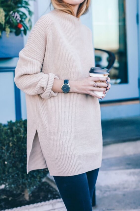 Blonde woman in a blush pink oversized sweater and blue skinny jeans