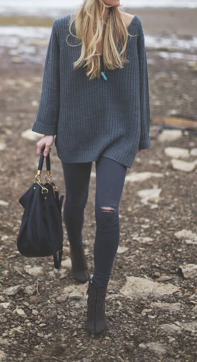 Blonde woman in an oversized navy blue sweater and ripped jeans