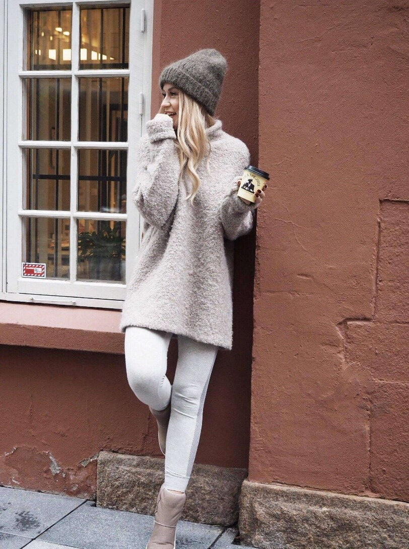 Blonde woman in white track pants and an oversized beige mohair sweater