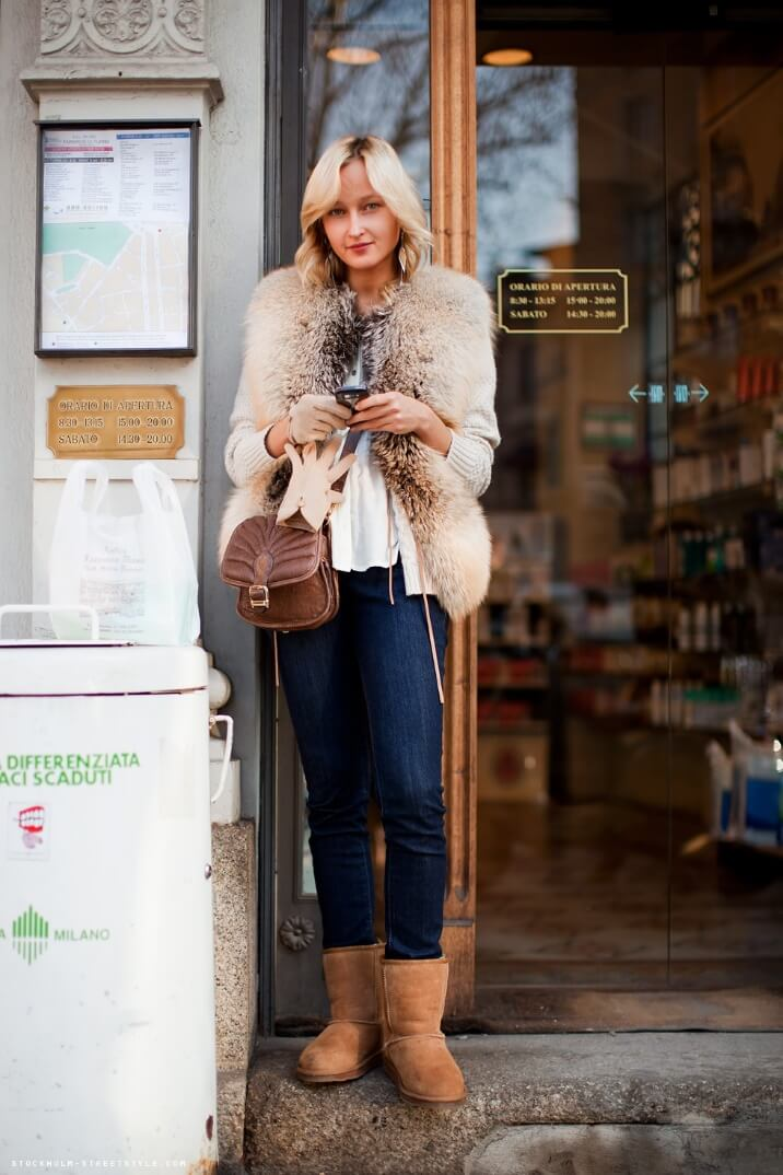 Blonde woman with short hair wearing blue jeans, a fur coat, and Ugg boots