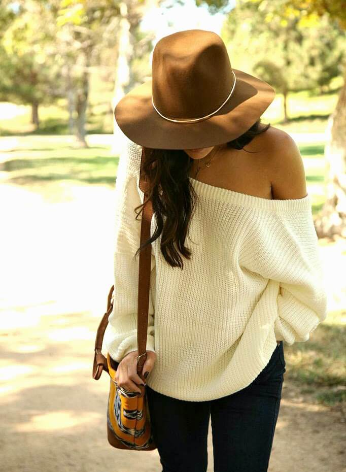 Brunette in cream oversized sweater and dark blue skinny jeans and floppy hat