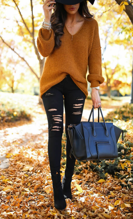 Brunette woman in an oversized mustard sweater and black ripped jeans