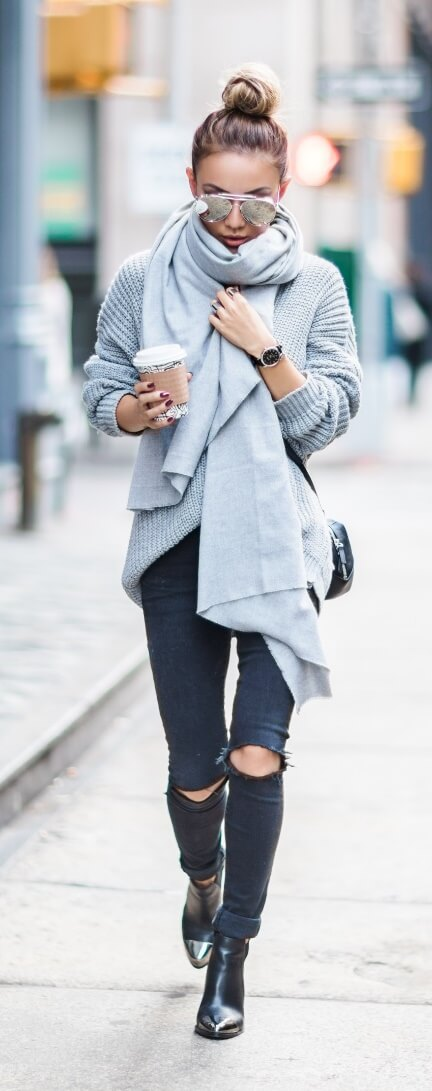 Chic woman in black ripped jeans and a grey oversized sweater