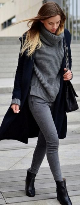 Classy brunette in grey skinny jeans, a black coat and an oversized sweater