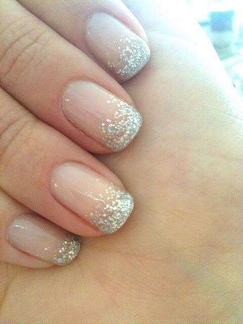 Clear manicure with silver glitter tips concentrated at the top of the nail